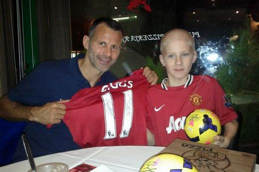 Ryan Giggs handing over a signed shirt and footballs to Levi